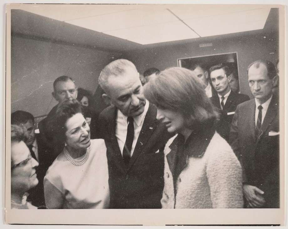 Lyndon Johnson, flanked by Lady Bird Johnson and Jacqueline Kennedy, aboard Air Force One. 1963