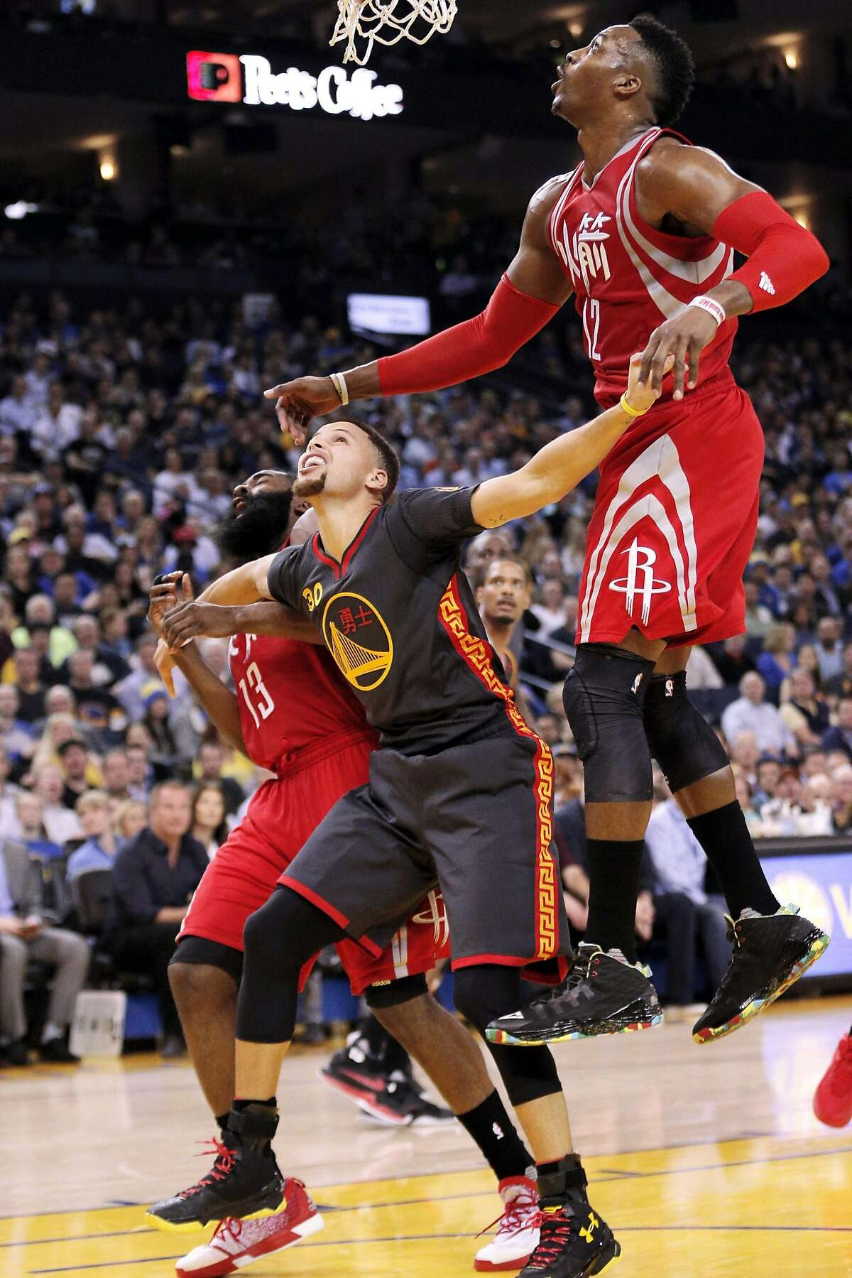 Stephen Curry (30) tries to box out Dwight Howard (12) and James Harden (13) from a rebound during the first half of the game between the Golden State Warriors and the Houston Rockets at Oracle Arena in Oakland, Calif., on Tuesday, February 9, 2016.