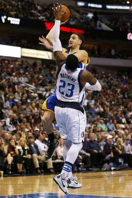 Golden State Warriors guard Klay Thompson (11) shoots in front of Dallas Mavericks guard Wesley Matthews (23) during the first half an NBA basketball game, Wednesday, Dec. 30, 2015, in Dallas. (AP Photo/Jim Cowsert)