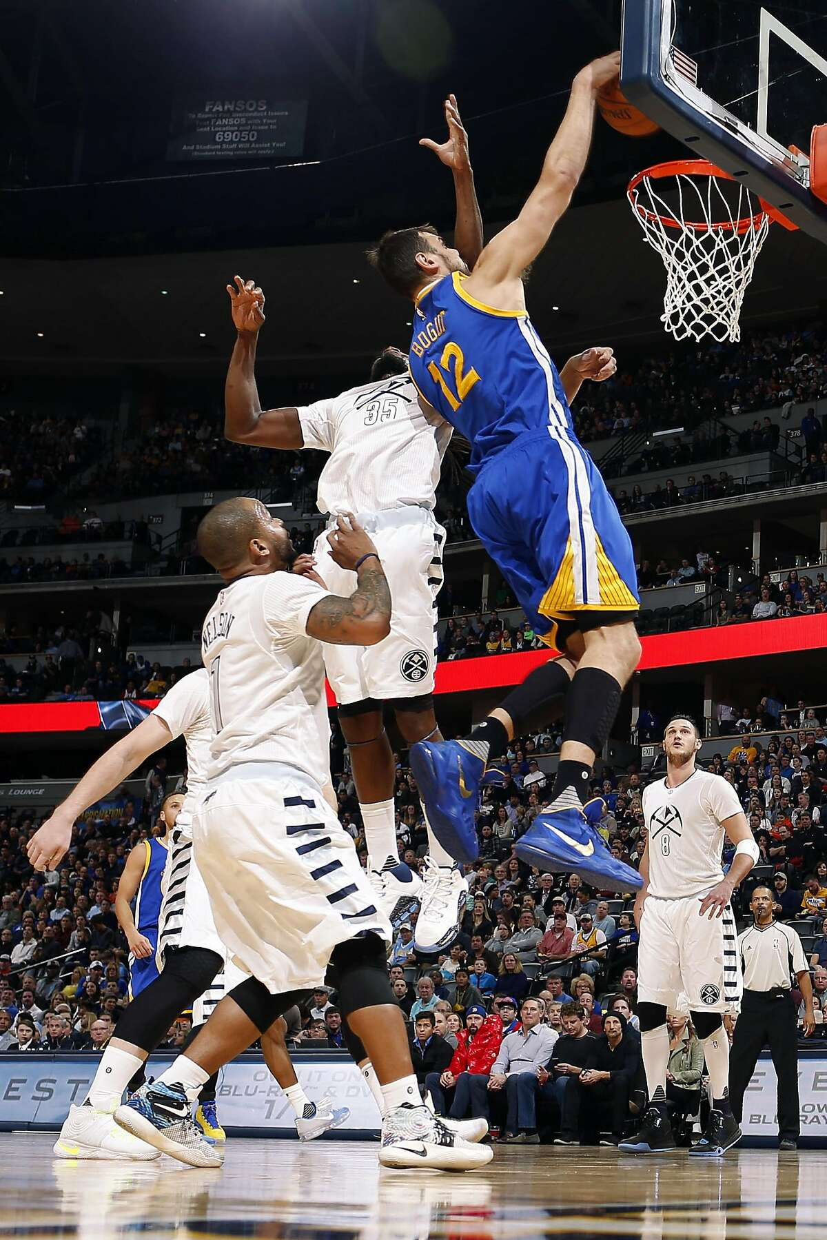 Golden State Warriors center Andrew Bogut, right, of Australia, dunks the ball for a basket as Denver Nuggets forward Darrell Arthur, center, and guard Jameer Nelson defend during the first half of an NBA basketball game Wednesday, Jan. 13, 2016, in Denver. (AP Photo/David Zalubowski)