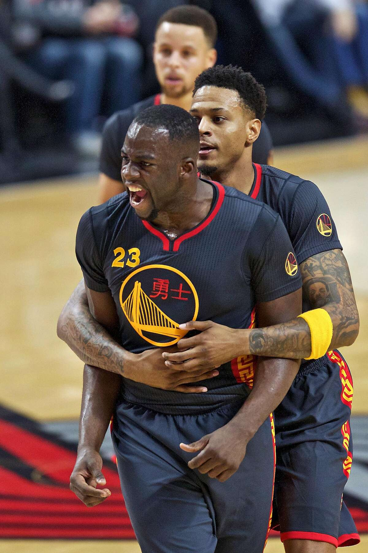 Golden State Warriors forward Draymond Green, left, reacts to a foul call and is held back by forward Brandon Rush, right, during the first half of an NBA basketball game against the Portland Trail Blazers in Portland, Ore., Friday, Feb. 19, 2016. (AP Photo/Craig Mitchelldyer)