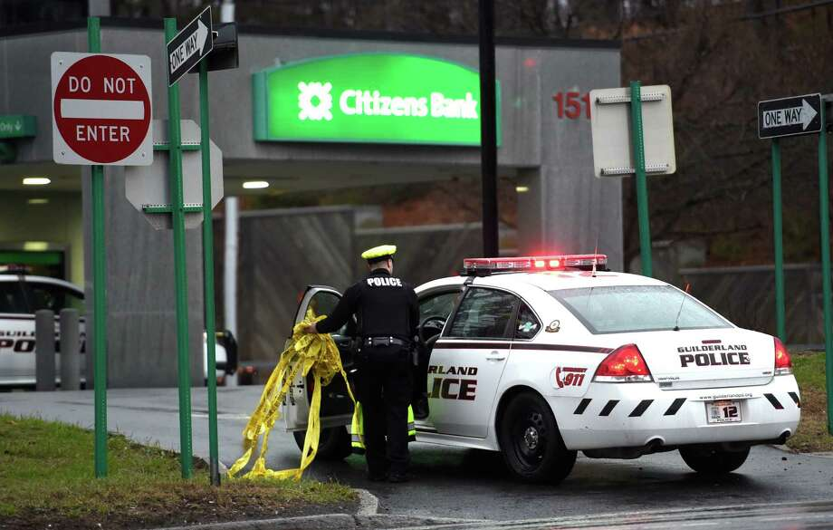 A Guilderland police officer removes crime scene tape at the site of a fatal car accident at the Citizens Bank at the corner of Western Ave and Schoolhouse Road early morning  April 12, 2016 in Guilderland, N.Y.    (Skip Dickstein/Times Union) Photo: SKIP DICKSTEIN