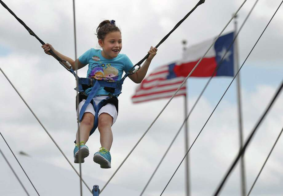"Sadie Lynn Delk gets a sky-high view as she is suspended from wires at the 2014 43rd Texas Folklife Festival at the Institute of Texan Cultures. The facility is being considered as the site for the proposed Triple-A baseball stadium in San Antonio. A reader says ""no way."" Photo: Kin Man Hui /San Antonio Express-News / ©2014 San Antonio Express-News"
