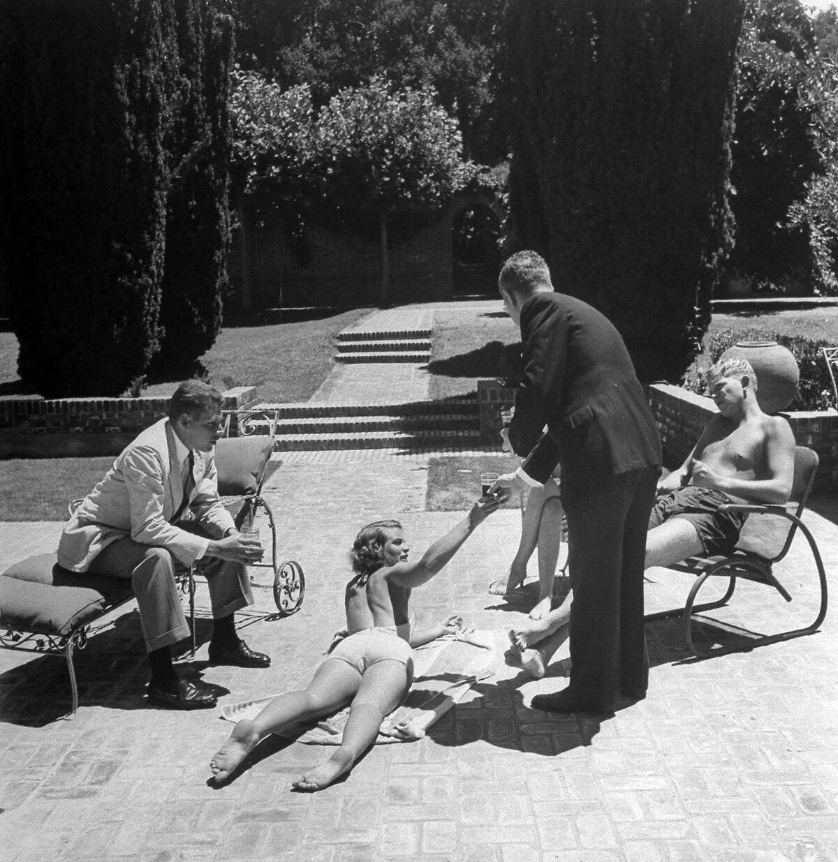 Simone Hotaling gets a drink from a butler at the Filoli estate pool in Woodside, California, 1947.