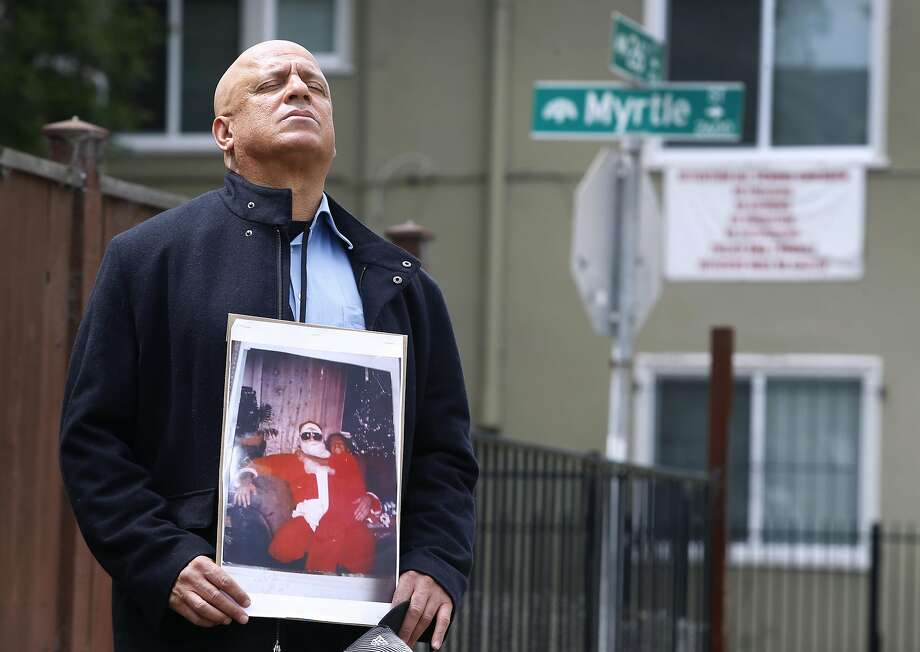 Donald Lacy, holding a photo of himself with daughter LoEshe Adanma Lacy, revisits the site of her slaying. Photo: Paul Chinn, The Chronicle