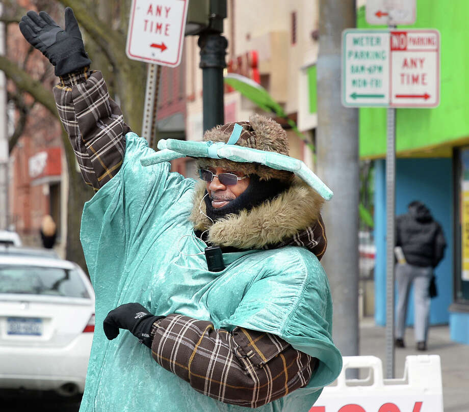 """Vernon Dortch, of Albany, a Liberty Tax Service """"waver,"""" who dons the foam Liberty torch hat and green costume as he waves, spins and struts his stuff on Central trying to attract last-minute tax filers Wednesday April 6, 2016 in Albany, NY.  (John Carl D'Annibale / Times Union) Photo: John Carl D'Annibale / 10036079A"""