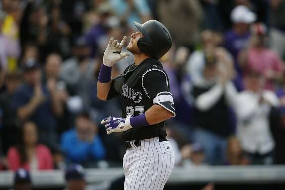 In this Sunday, April 10, 2016, photograph, Colorado Rockies' Trevor Story gestures as he crosses home plate after hitting a solo home run against the San Diego Padres in the eighth inning of a baseball game in Denver. Story's first week in the major leagues was one for the record books as the shortstop set a slew of records including hitting home runs seven times in his first six career games. (AP Photo/David Zalubowski)