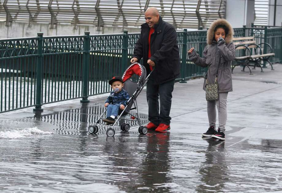 Nov. 2015: Along San Francisco's Embarcadero, Isaac Villareal, with nephew Jamison McCall in a stroller and his daughter Araya, navigate through a sidewalk during a king tide. Photo: Paul Chinn, The Chronicle / ONLINE_YES