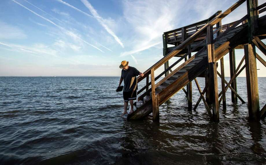 October 2014: On Tybee Island, Ga., visitor Fran Glod walks down the steps to the beach which is covered by an king tide high tide. Photo: Stephen B. Morton, Associated Press / FR56856 AP