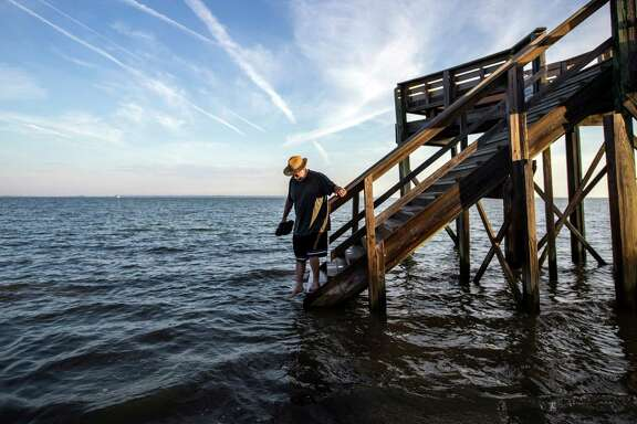 Visiting the area for the first time, 64-year-old Fran Glod of Oswego, N.Y, walks down the steps to the beach which is covered by a king tide high tide, Thursday, Oct. 9, 2014, on Tybee Island, Ga. The annual king tide is the year's highest astronomical tide when the alignment of the full moon cause higher than normal tides along the coast. (AP Photo/Stephen B. Morton)
