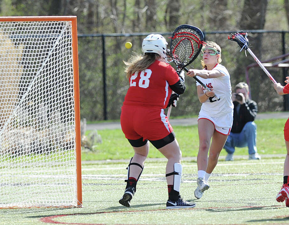 New Canaan's Catherine Granito, right, scores a goal getting the ball past Greenwich goalie Kathryn Crouchley (#28), left, during the girls high school lacrosse match between New Canaan High School and Greenwich High School at New Canaan, Conn., Tuesday, April 12, 2016. Photo: Bob Luckey Jr. / Hearst Connecticut Media / Greenwich Time