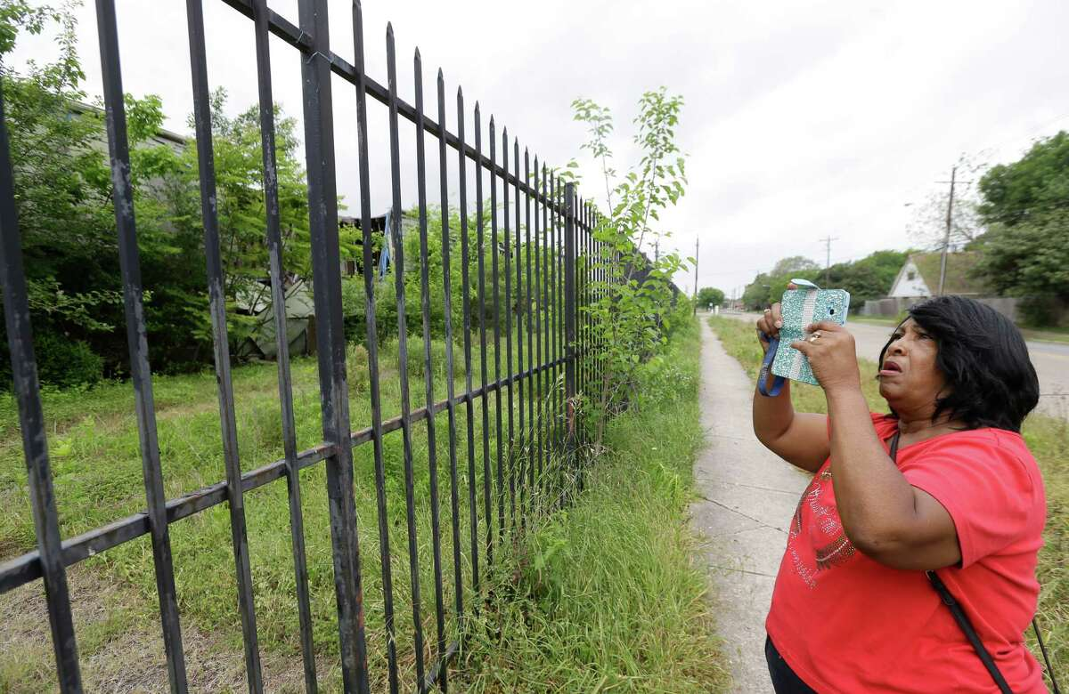 Community activist Sandra Hines takes a photo of the Crestmont West Apartments on Monday.