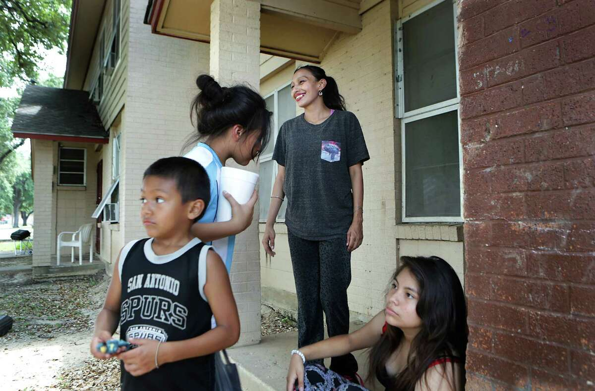Patricia Martinez smiles at a visitor. With her on the porch of their Cassiano Homes unit are her children, Paul (from left), Rebekah Martinez, and Jerilyn.