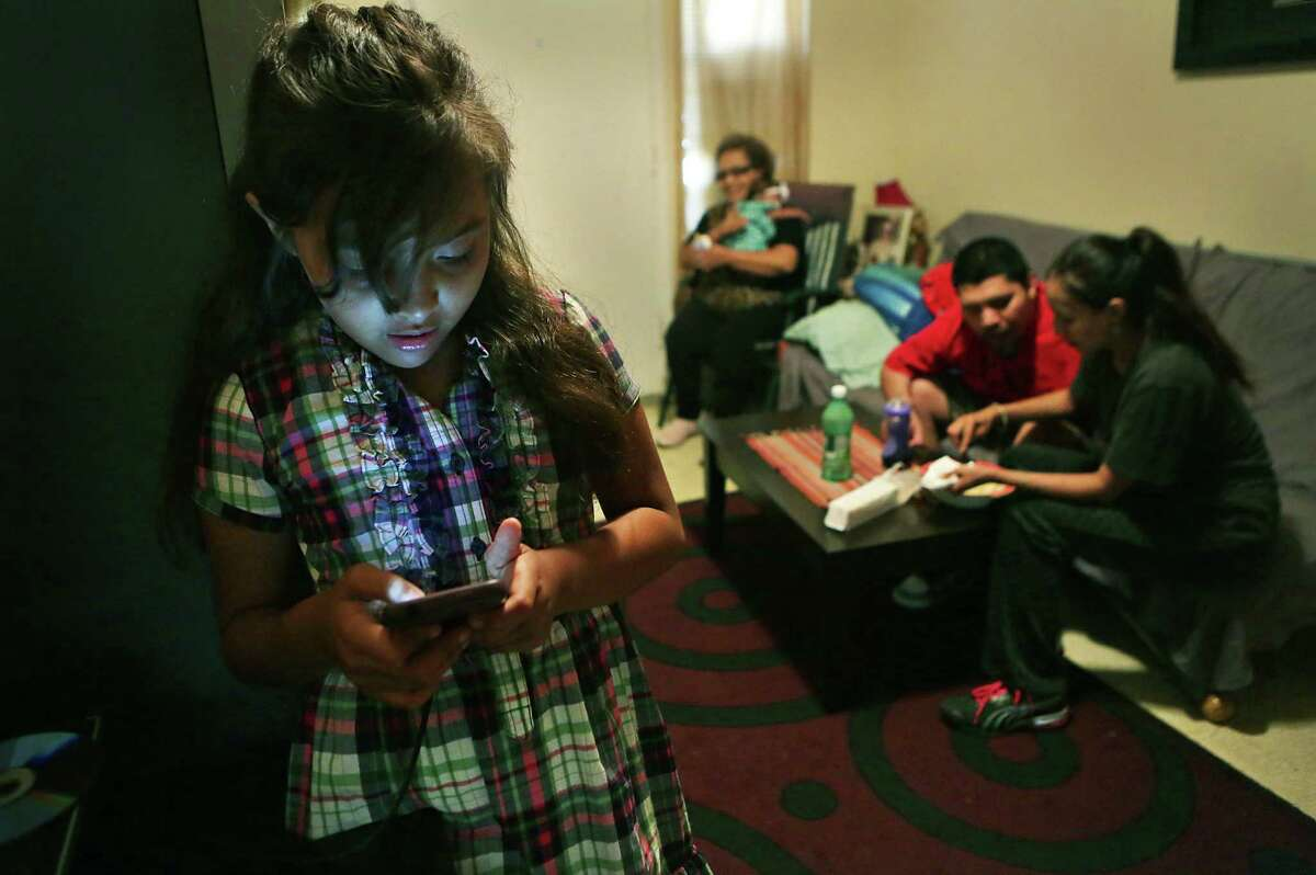 Rebekah Martinez, 10, looks at her mom's cellphone as her mother, Patricia Martinez (right) helps her disabled husband, Jerry Martinez, with a snack. Patricia's mother, Maria Diaz, holds the family's youngest, Unique.