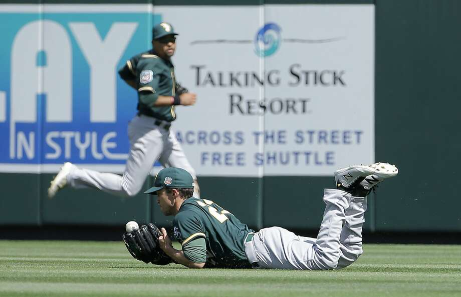 Oakland Athletics right fielder Sam Fuld, bottom, catches an RBI sacrifice fly hit by Colorado Rockies' DJ LeMahieu during the second inning of a spring training baseball game in Scottsdale, Ariz., Tuesday, March 15, 2016. (AP Photo/Jeff Chiu) Photo: Jeff Chiu, AP