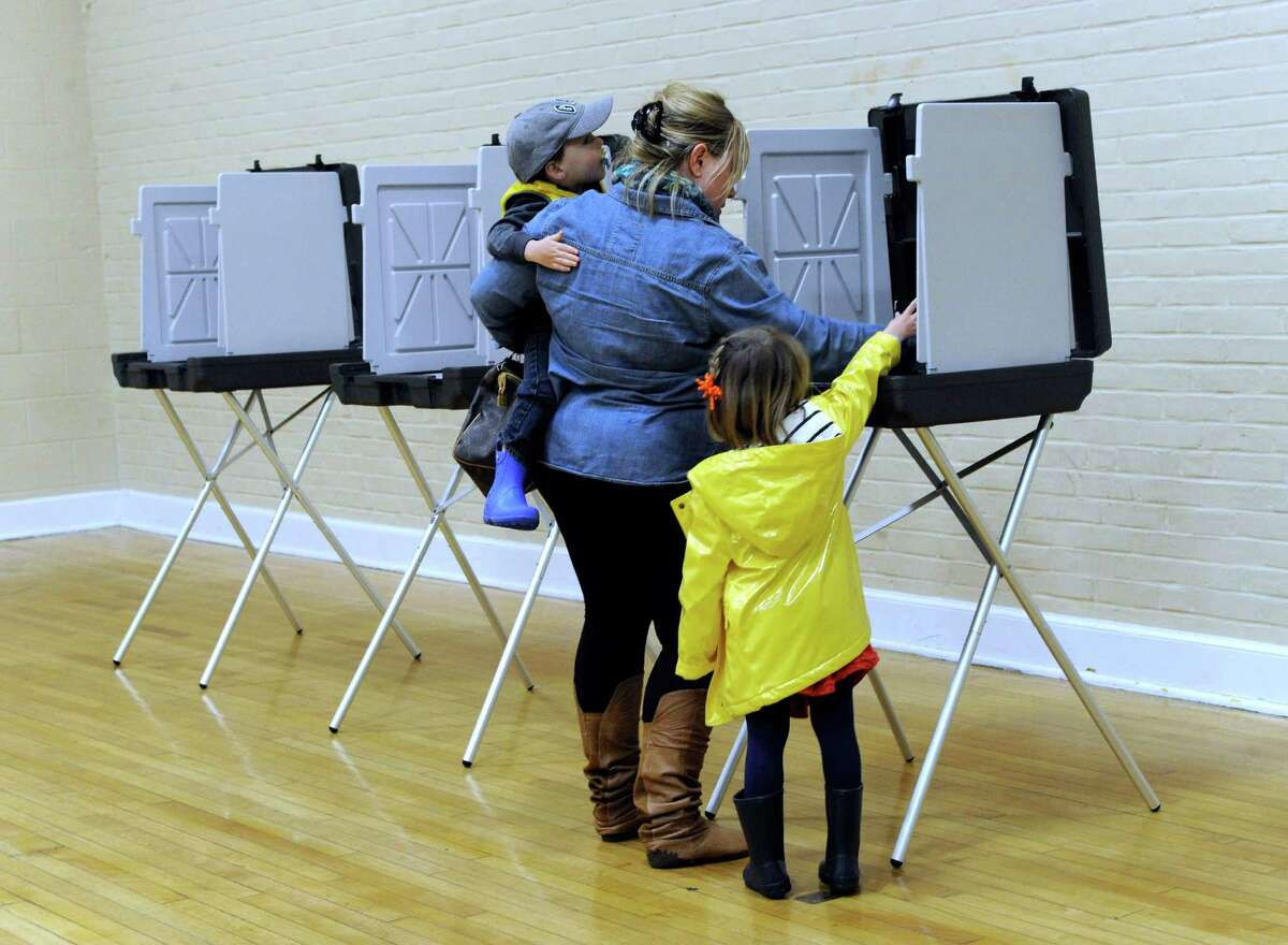 Carrie Sirois, with her children, Grayson, 2, and Reese, 4, votes in Tuesday's budget referendum in Bethel at the Municipal Center.