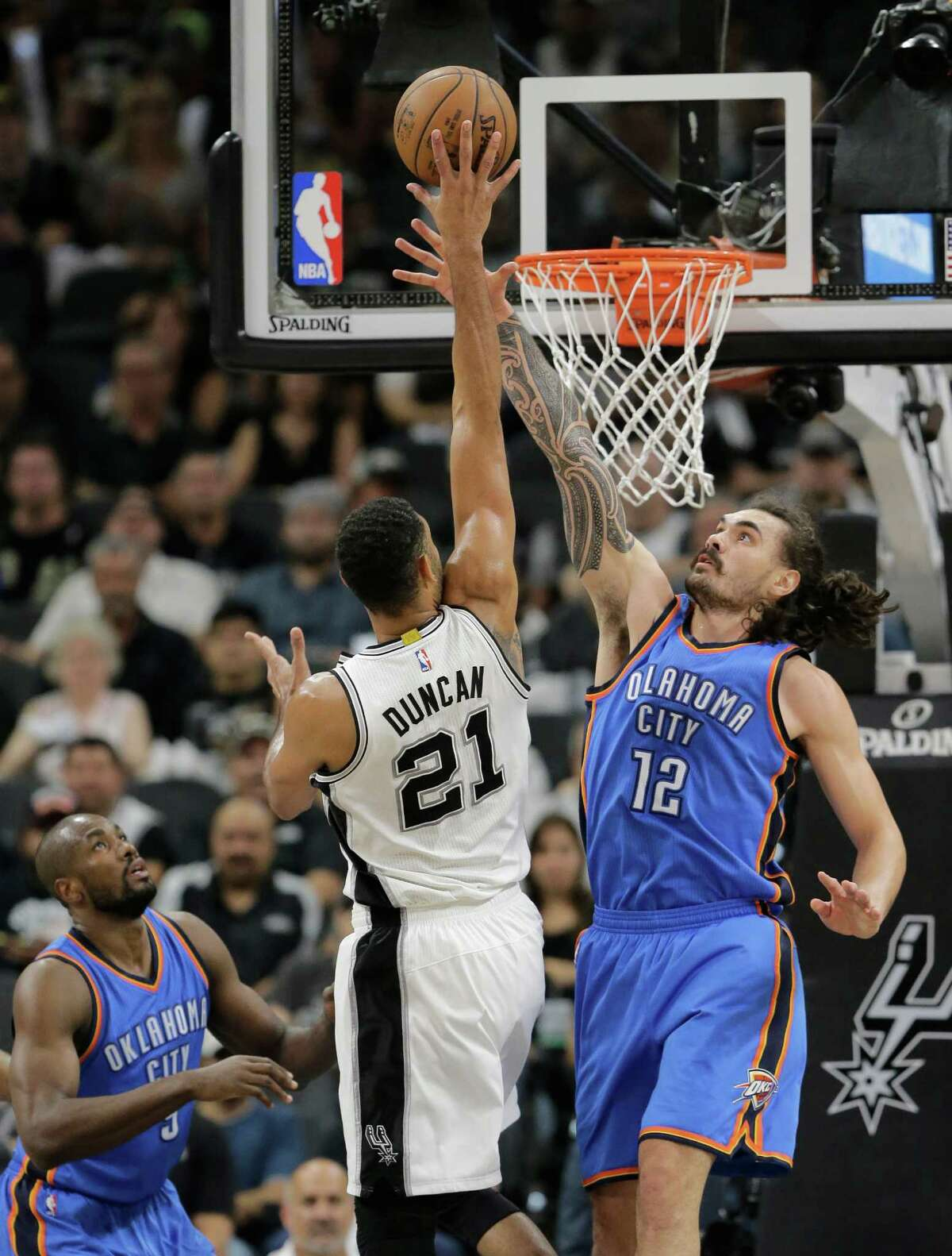 San Antonio Spurs forward Tim Duncan (21) shoots over Oklahoma City Thunder center Steven Adams (12) during the first half in Game 5 of a second-round NBA basketball playoff series, Tuesday, May 10, 2016, in San Antonio. (AP Photo/Eric Gay)