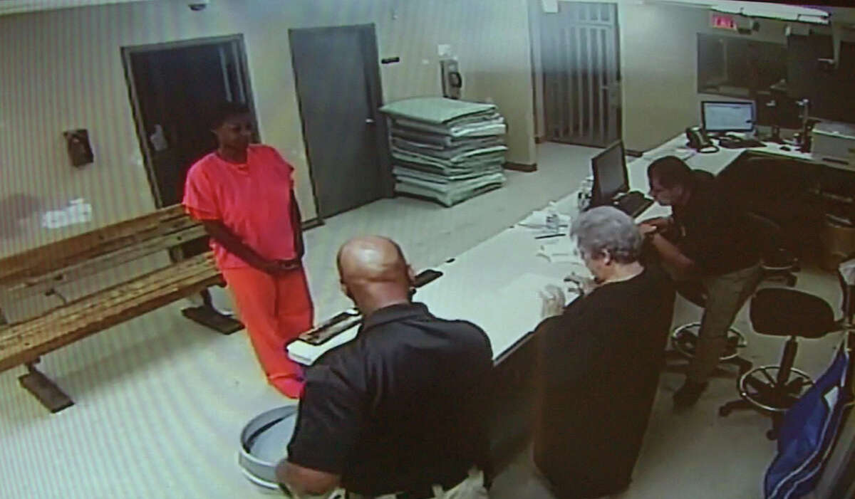 In this image made from video provided by the Waller County Sheriff's Office, Sandra Bland stands before a desk at the Waller County Jail. Bland was found dead in her cell three days after she was arrested by a state trooper who said she failed to signal while changing lanes.
