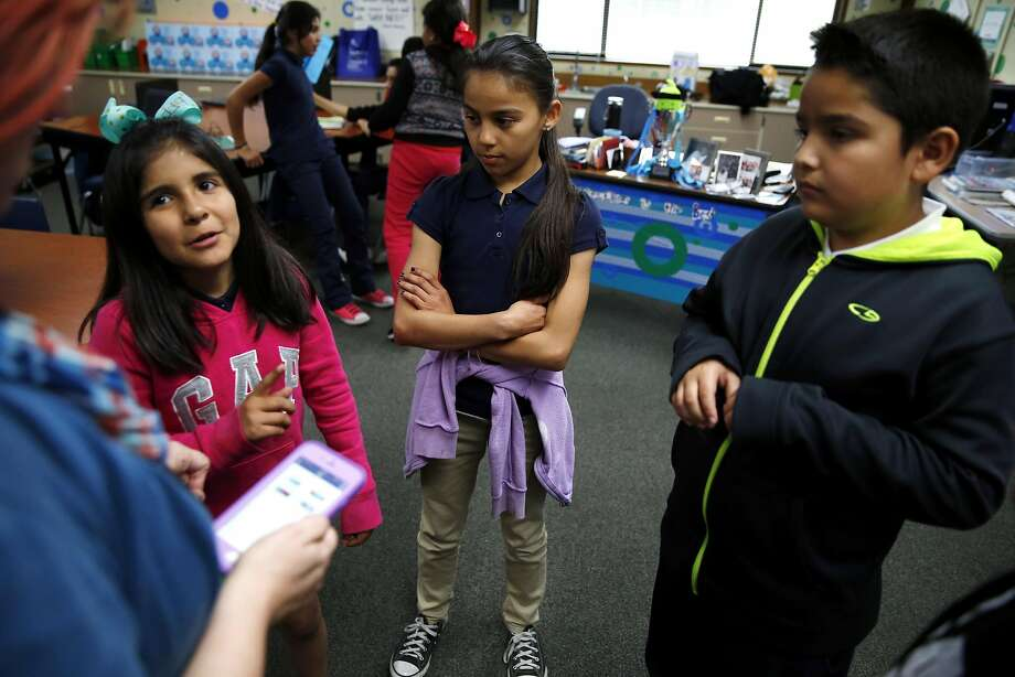 Fernanda Santa Cruz (left), Alexa Villalobos De La Torre and Max Valle summarize a video they watched to teacher Jen Ellison. She uses ClassDojo to award points based on their responses. Photo: Connor Radnovich, The Chronicle