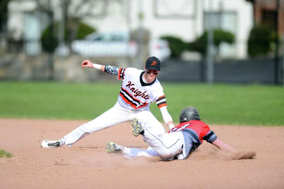 Stamford High shortstop Jay DeVito tags out New Canaan's Michael Svagdis as he tries to steal second base during the Stamford Black Knights' home opener against New Canaan on Monday. Photo: Michael Cummo / Hearst Connecticut Media / Stamford Advocate