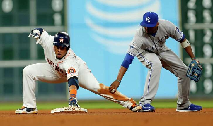 Houston Astros center fielder Carlos Gomez (30) grabs onto second base after his double as Kansas City Royals shortstop Alcides Escobar (2) tries to tag him during the fourth inning of an MLB game at Minute Maid Park, Tuesday, April 12, 2016, in Houston.