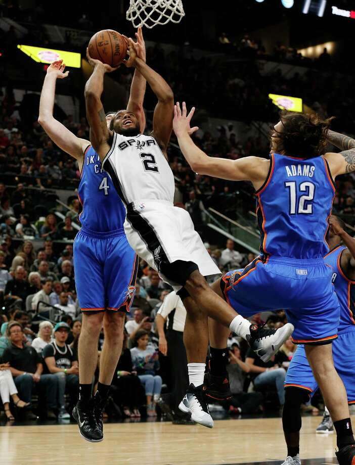 Spurs' Kawhi Leonard (02) goes up for a shot against Oklahoma City Thunder's Nick Collison (04) and Steven Adams (12) at the AT&T Center on Tuesday, Apr. 12, 2016. Spurs defeated the Thunder, 102-98, in overtime. (Kin Man Hui/San Antonio Express-News) Photo: Kin Man Hui, Staff / San Antonio Express-News / ©2016 San Antonio Express-News