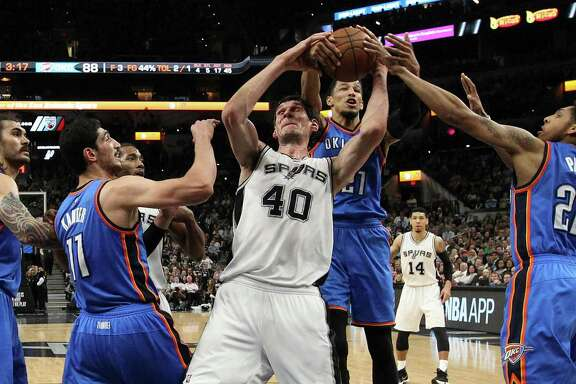 Spurs' Boban Marjanovic battles for rebound against Oklahoma City Thunder's Steven Adams (12), Enes Kanter (11), Andre Roberson (21) and Cameron Payne (22) at the AT&T Center on April 12, 2016.