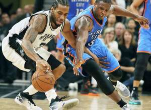 Dion Waiters tries unsuccessfully to steal the ball from Kawhi Leonard as the Spurs host Oklahoma at the AT&T Center on April 12, 2016.
