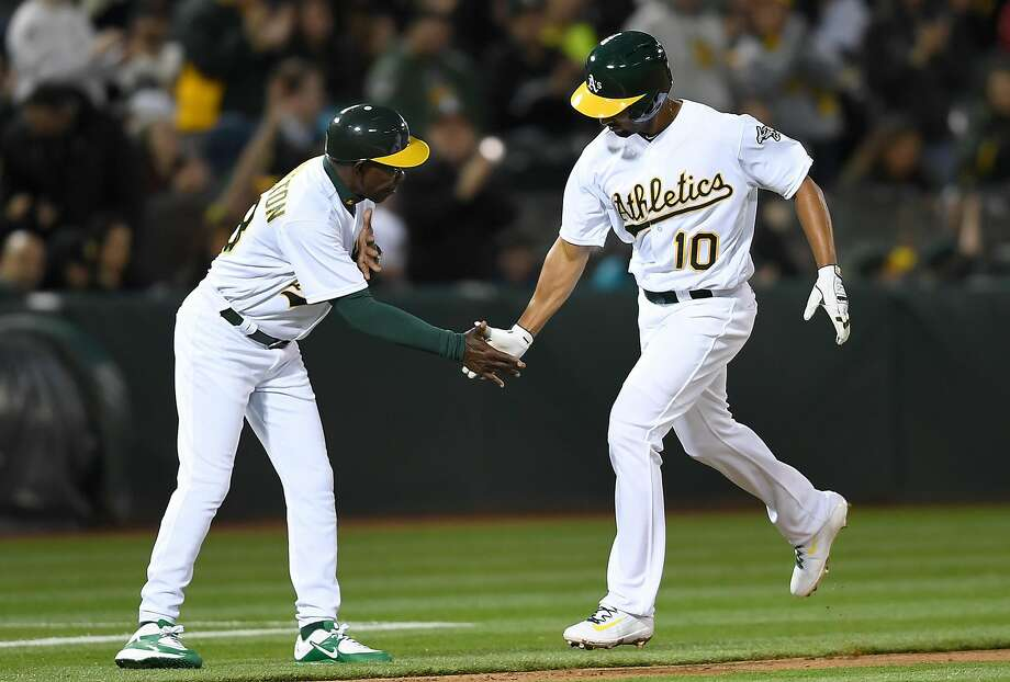 Marcus Semien is met by third-base coach Ron Washington in the third inning after the first of his two solo home runs. Photo: Thearon W. Henderson, Getty Images