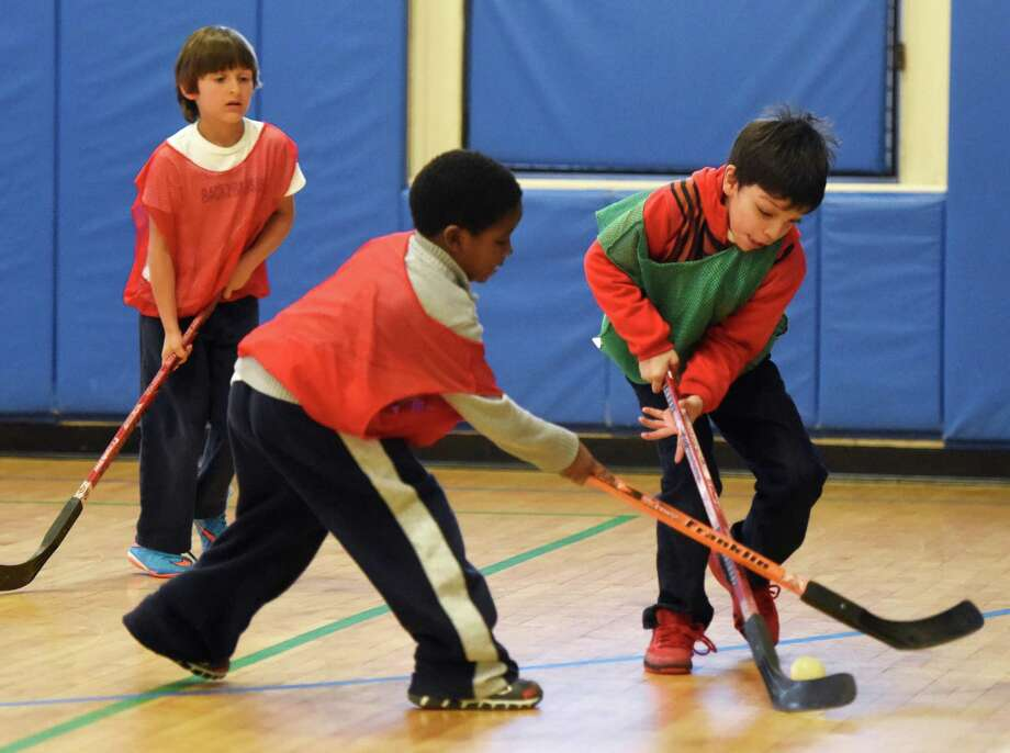 Grant Wall, center, 6, and Kayden Jimenez, right, 7, battle for the puck as Antonio Mitkov, left, 6, watches during a game of floor hockey at the Boys & Girls Club in Greenwich in January. On Wednesday, sales at the Port Chester Buffalo Wild Wings will help the club promote team sports to kids. Photo: Tyler Sizemore / Hearst Connecticut Media / Greenwich Time
