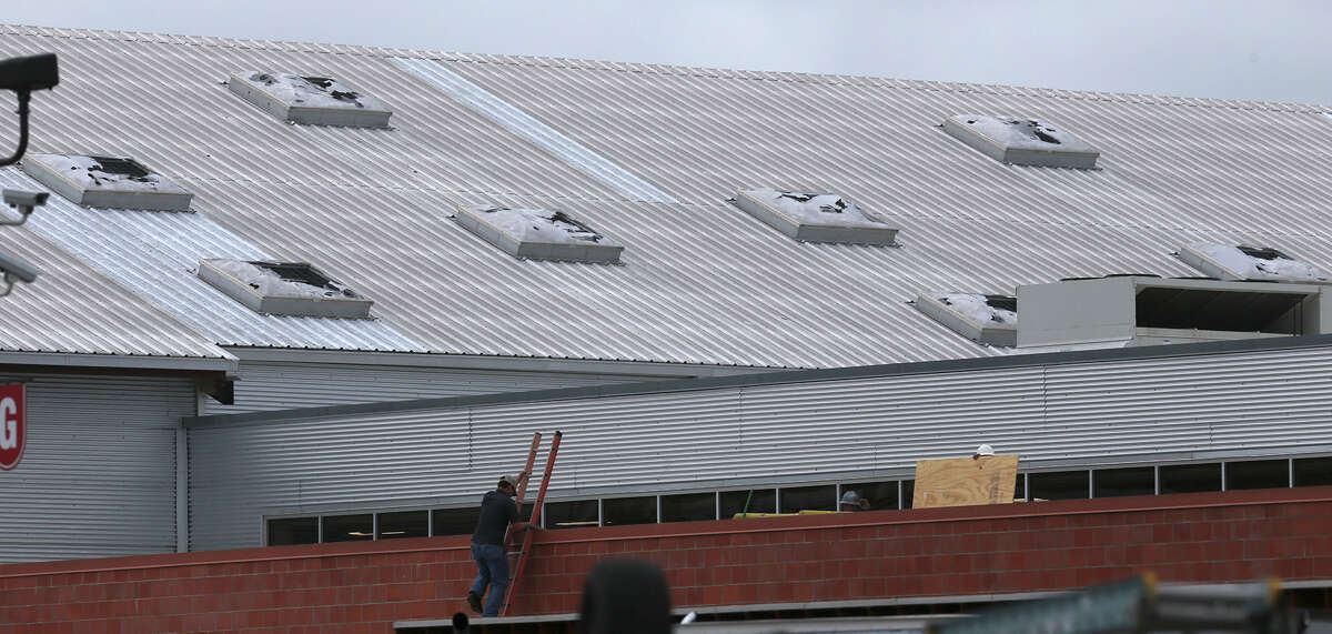 A worker (bottom, center) climbs a ladder Wednesday April 13, 2016 on the roof of the H-E-B plus! at Loop 1604 and Bandera after hail moved through the area last night shattering skylights on the building and damaging cars in the area.