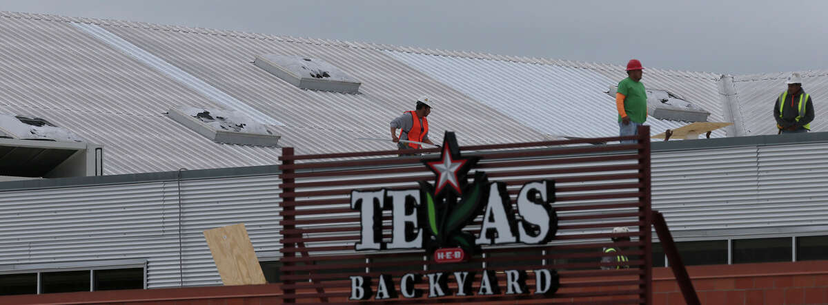 Workers do repairs Wednesday April 13, 2016 on the roof of the H-E-B plus! at Loop 1604 and Bandera after hail moved through the area last night shattering skylights on the building and damaging cars in the area.