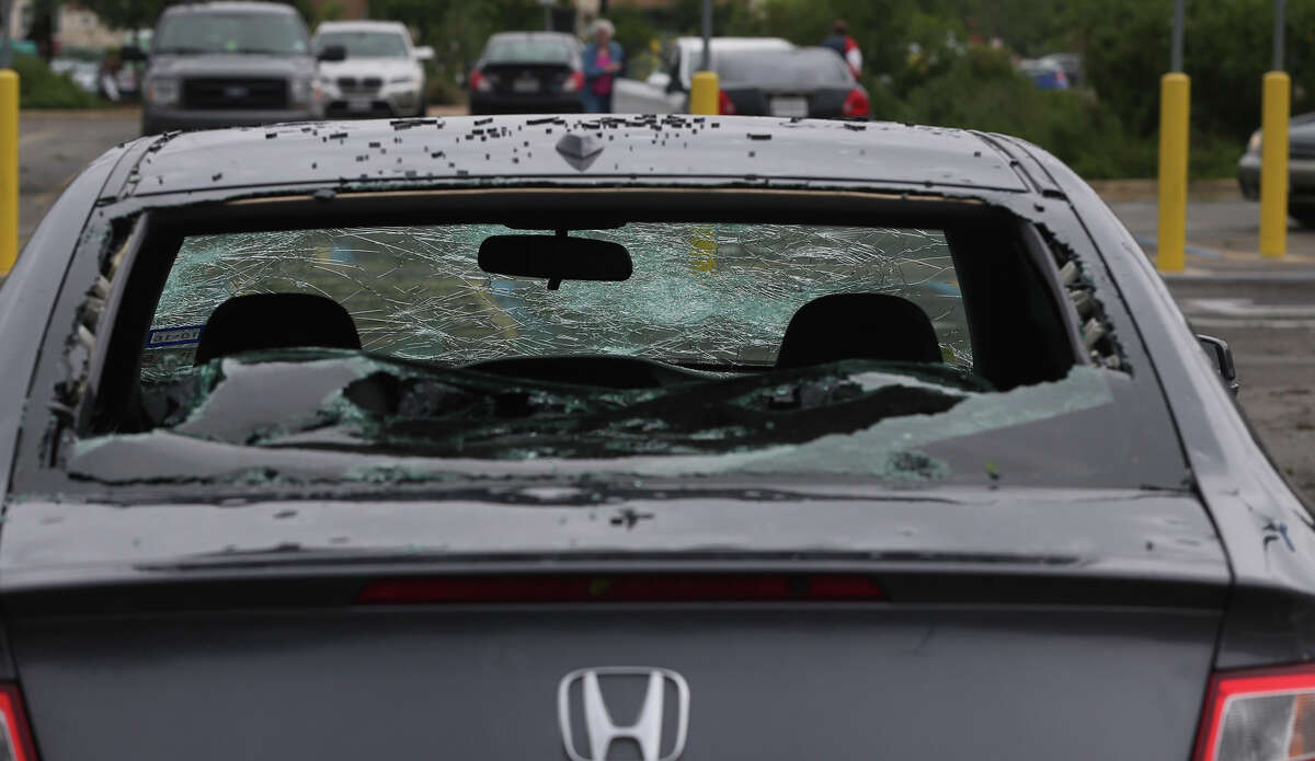 A Honda damaged by hail is in the Wal-Mart parking lot in Helotes after a storm swept through the area last night.
