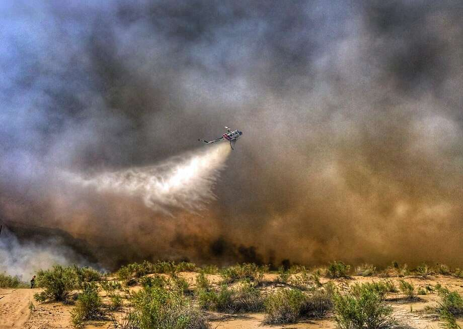 A helicopter drops water on a wildfire endangering a trailer park near Needles (San Bernardino County) in early April. Retirees and urbanites seeking more pastoral settings are pushing into outlying places that firefighters must now protect. Photo: SAN BERNARDINO COUNTY FIRE DEPARTMENT, NYT