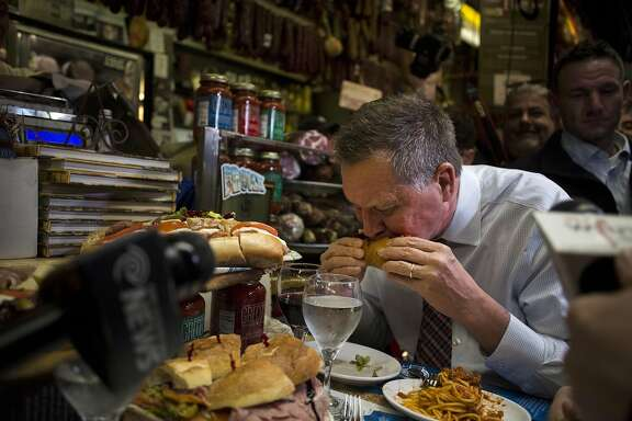 John Kasich, governor of Ohio and 2016 Republican presidential candidate, eats a sandwich at Mike's Deli during a campaign stop in the Bronx borough of New York, U.S., on Thursday, April 7, 2016. Kasich, the third Republican in the race, has only won his home state and was lagging well behind Trump and Cruz in Wisconsin polls. Photographer: John Taggart/Bloomberg *** Local Caption *** John Kasich