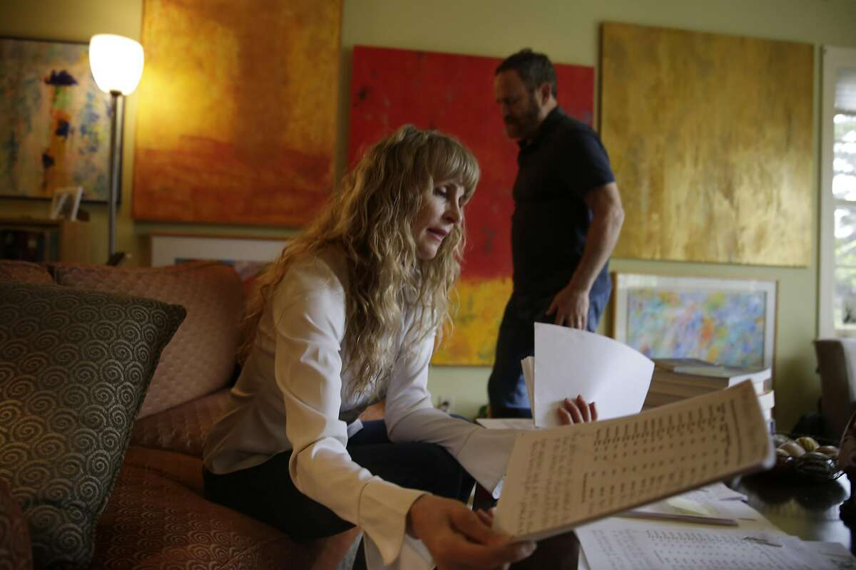 """JoAnne """"JoAnneh"""" Nagler (l to r) looks over some of the bills, tax forms and notes regarding the tax issue between Kaiser and Covered California that has left them unable to finish their taxes as Michael Nagler walks behind her at their home on Tuesday, April 12, 2016 in Burlingame, California."""