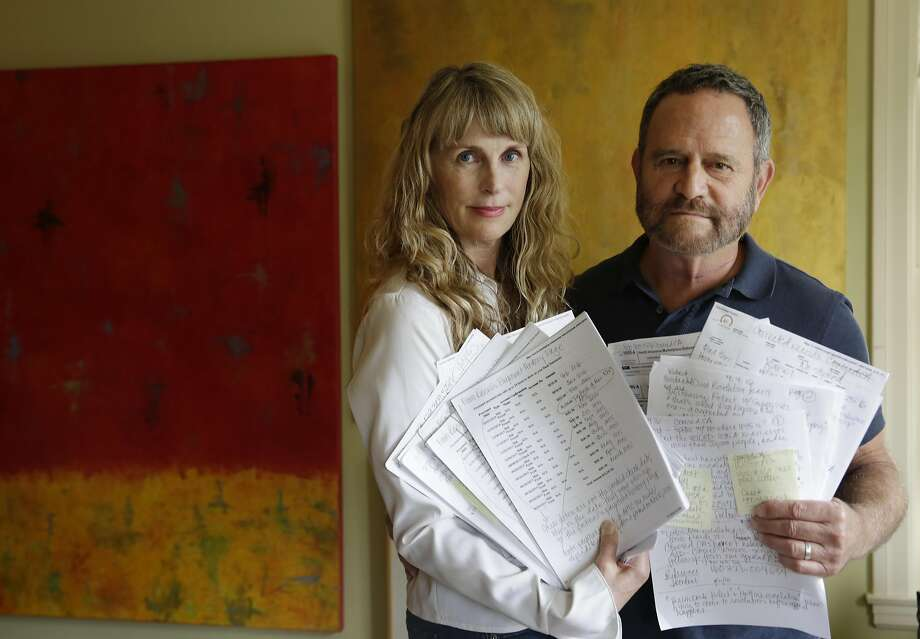 """JoAnne """"JoAnneh"""" Nagler (l to r) and Michael Nagler hold some of the bills, tax forms and notes regarding the tax issue between Kaiser and Covered California that has left them unable to finish their taxes on Tuesday, April 12, 2016 in Burlingame, California. Photo: Lea Suzuki, The Chronicle"""