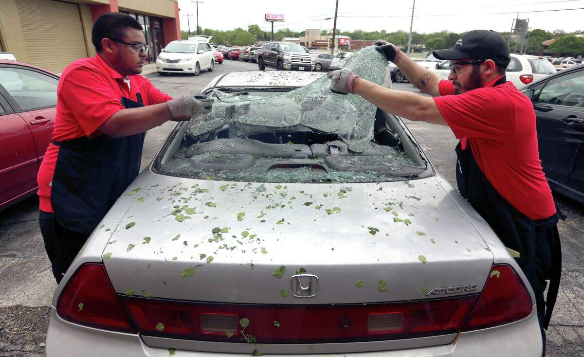 Safelite automotive glass repair company employees Erik White, left, and Jacob Escobar remove broken glass Wednesday, April 13, 2016 at the company's I-10 store location after a widespread overnight hail storm broke windshields throughout large swaths of the city.