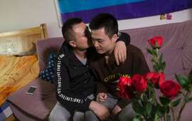 This photo taken on April 12, 2016 shows Sun Wenlin (R) and his partner Hu Mingliang sitting on a sofa at their rental house in Changsha, central China's Hunan province.  A Chinese court ruled against two men seeking to marry, it said on April 13, as more sexual minorities push for equal rights in the country. Sun Wenlin, 27, sued a civil affairs bureau after it refused to grant him and his partner, Hu Mingliang, a marriage certificate. / AFP PHOTO / STR / China OUTSTR/AFP/Getty Images