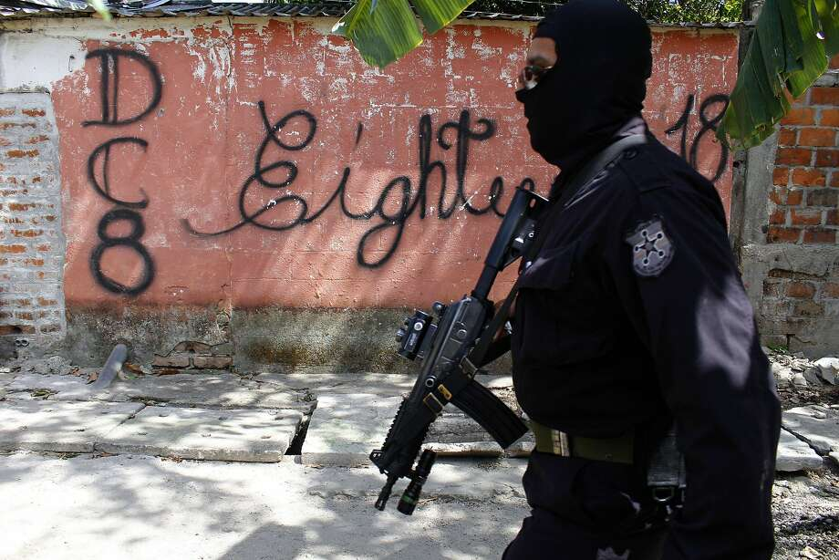 A masked police officer patrols a gang-controlled neighborhood in San Salvador last week. Photo: Alex Pe�a, AP