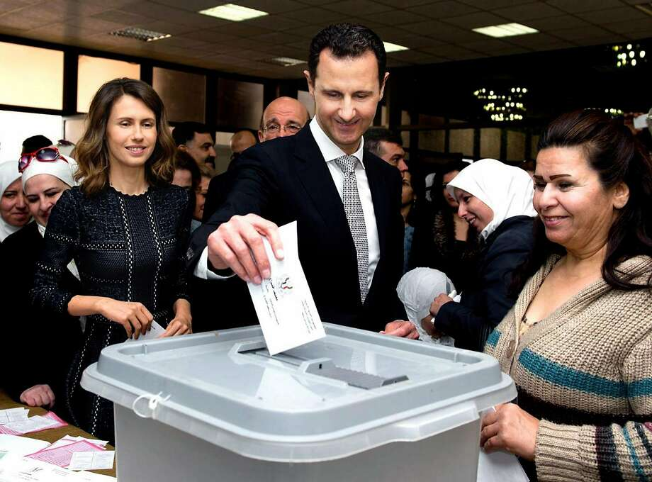 Syrian President Bashar Assad casts his ballot in parliamentary elections as his wife, Asma (left), waits her turn to vote in Damascus. The country's bloody civil war is in its fifth year. Photo: Uncredited, AP