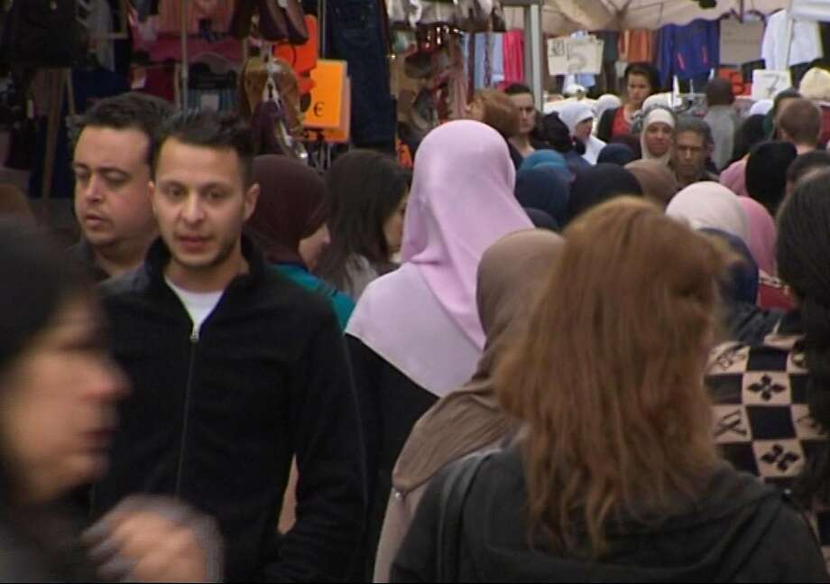 Salah Abdeslam (left), a key suspect in the Paris attacks, is seen in a video walking down a crowded street in Brussels in 2014. Photo: AP