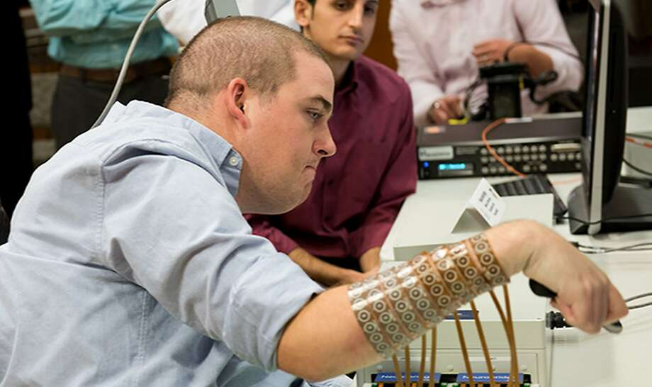 """In this handout picture obtained from the journal """"Nature"""" on April 13, 2016 shows Ian Burkhart, 24, who was paralyzed from the shoulders down after a diving accident in 2010, undertaking tasks after regaining the use of his hand through the use of neural bypass technology at the Ohio State University Wexner Medical Center.   Six years after a diving accident left him paralysed, Ian Burkhart can use his right hand, controlled by his mind and aided by computer software, to stir his own coffee, a groundbreaking trial reported on April 13, 2016. The feat was made possible with a pea-sized chip in the 24-year-old's head to decypher his brain signals and rerouting them to the finger, hand and wrist muscles -- bypassing the damaged spinal cord.The muscles are stimulated by an electrode sleeve worn on the right forearm, with which Burkhart can now also swipe a credit card, grasp a container and pour from it, and play the cords of a guitar video game. / AFP PHOTO / NATURE PUBLISHING GROUP AND AFP PHOTO / Handout / RESTRICTED TO EDITORIAL USE - MANDATORY CREDIT """"AFP PHOTO / Ohio State University Wexner Medical Center/ Batelle"""" - NO MARKETING NO ADVERTISING CAMPAIGNS - DISTRIBUTED AS A SERVICE TO CLIENTSHANDOUT/AFP/Getty Images Photo: HANDOUT, AFP/Getty Images"""