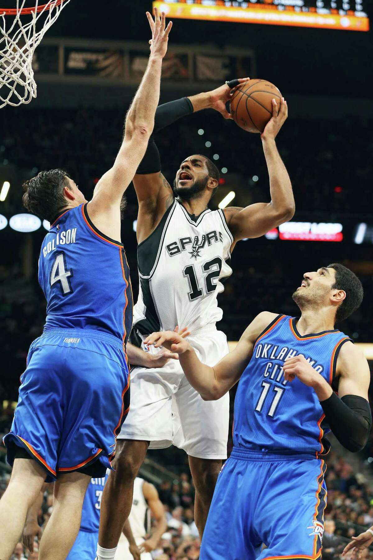 LaMarcus Aldridge takes it up over Nick Collison as Enes Kanter waits on the floor as the Spurs host Oklahoma at the AT&T Center on April 12, 2016.