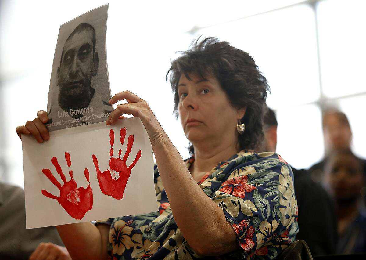 Lisa Prochello from San Francisco holds up a sign during a town hall meeting at the Union Local Hall regarding the San Francisco Police Department's officer-involved shooting of Luis Gongora, a 45-year-old homeless man in San Francisco, California on wednesday, april 13, 2016.