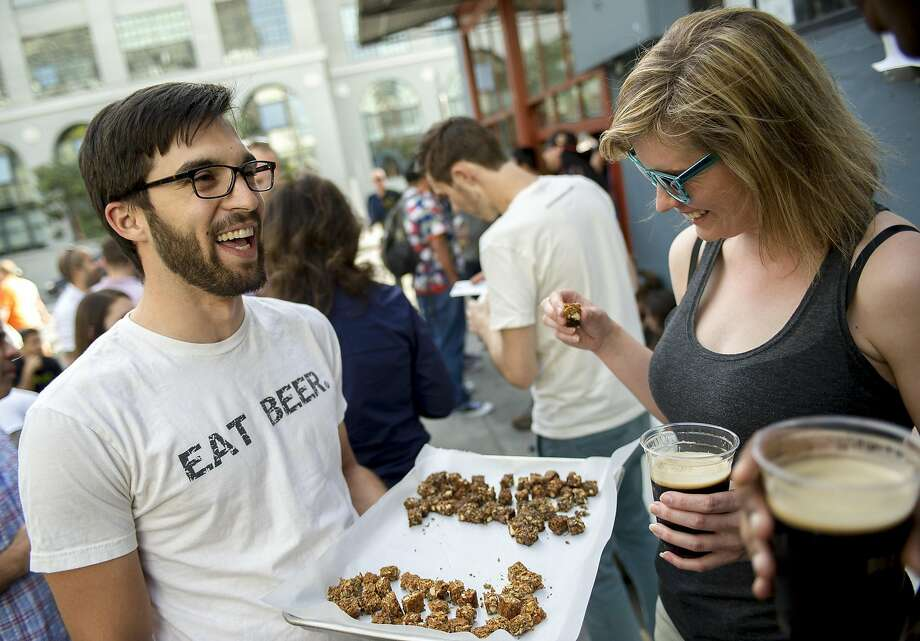 Danielle Lee, right, of New York City, takes a honey almond IPA granola bar sample from Dan Kurzrock, right, co-founder of Regrained, at 21st Amendment Brewery in San Francisco. Photo: Dan Evans