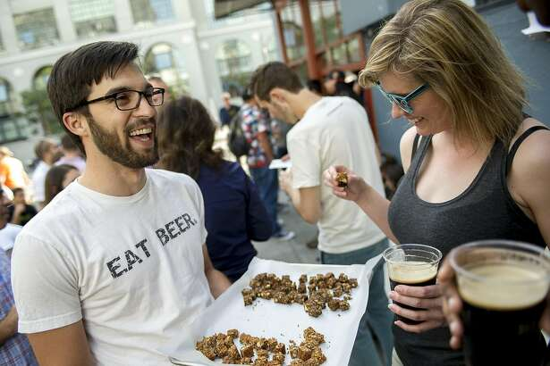 Danielle Lee, right, of New York City, takes a honey almond IPA granola bar sample from Dan Kurzrock, right, co-founder of Regrained, at 21st Amendment Brewery in San Francisco.