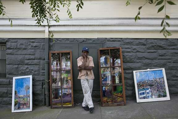 Artist and musician Chris Duke stands with some of his paintings near his home on Thursday, April 7, 2016 in San Francisco, Calif. Duke sells his art on Steiner street every weekend.
