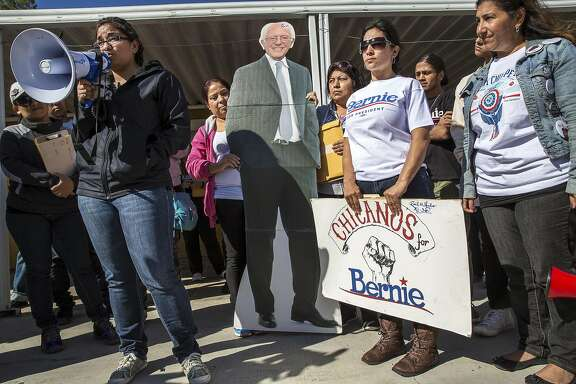 Maria Castro, left, speaks as campaign workers and supporters gather at Sen. Bernie Sanders' northeast campaign office for a rally and canvassing in Las Vegas, Feb. 18, 2016. (Monica Almeida/The New York Times)