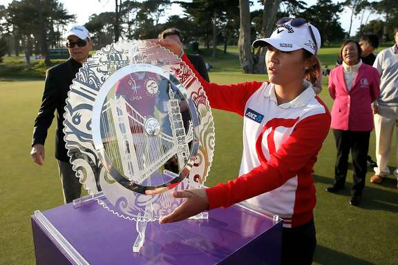 Lydia Ko picks up the champions trophy after her win of the 2015 the Swinging Skirts LPGA  Classic golf tournament at Lake Merced Golf Course in Daly City, Calif., on Sun. April 26, 2015.